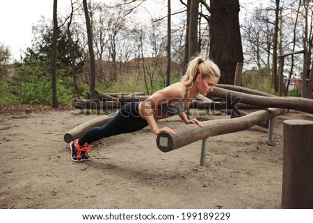 Tough young woman doing pushups on a log at park. Fit young woman exercising in woods. - stock photo