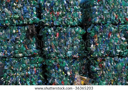 TOULOUSE, FRANCE - CIRCA 2009: Bales of green plastic bottles stacked at an undisclosed recycling facility circa 2009 in Toulouse. The plastic is gathered by color and type to be recycled. - stock photo