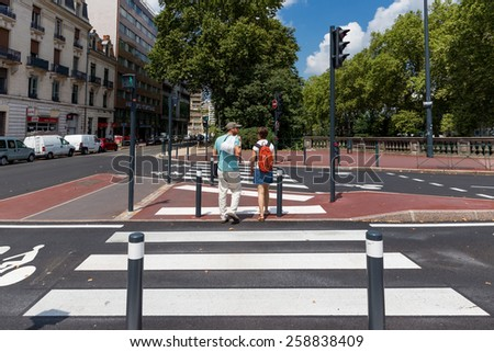 TOULOUSE, FRANCE - JULY 27, 2014: 2 locals crossing a zebra crossing. French government is trying to improve matters but French drivers still pay little attention to pedestrians and zebra crossings. - stock photo