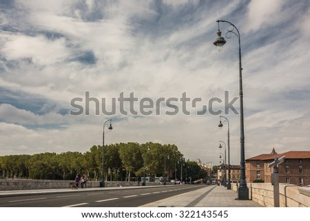 TOULOUSE, FRANCE - 13 SEPTEMBER 2015: Old bridge in Toulouse and unidentified people - stock photo