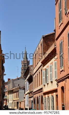 Toulouse in the south of France with typical architecture made of red bricks against bright blue sky - St Sernin basilica - stock photo