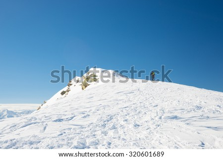 Tour skier hiking uphill towards the mountain summit under a bright sun with clear deep blue sky. Italian Alps. Concept of conquering adversities and reaching the target. - stock photo