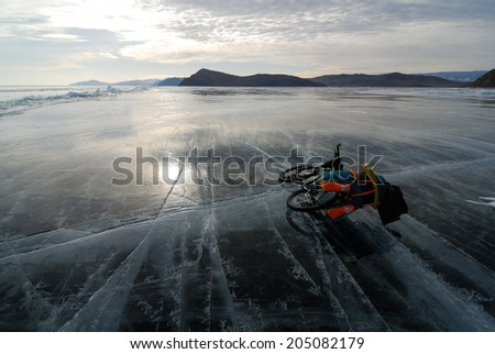 Touring mountain bike with pannier on the surface of frozen lake - stock photo