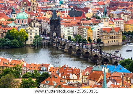 Tourism and sightseeing, view from above over famous sight of Prague Charles Bridge and Old Town Eastern tower. Good weather, summer day, river Vltava, red tiled roofs, crowd of tourists on the bridge - stock photo