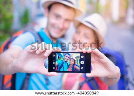 Tourism and technology. Traveling backpacker couple taking selfie on smartphone together outdoors. Focus on screen.