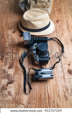 Tourism concept. Backpack, hat , binocular and old camera isolated on wooden background. - stock photo