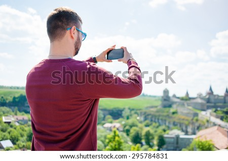 Tourism concept. Young man taking photo on smartphone while traveling by Europe. - stock photo