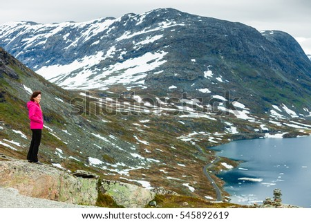 Tourism holidays and travel. Woman tourist standing near Djupvatnet lake, relaxing meditation with serene mountains view, Stranda More og Romsdal, Norway Scandinavia.