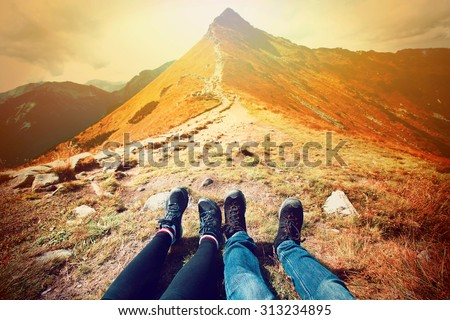 Tourism in mountains. A couple of tourists rest on the mountain path. Nature in mountains at autumn. - stock photo