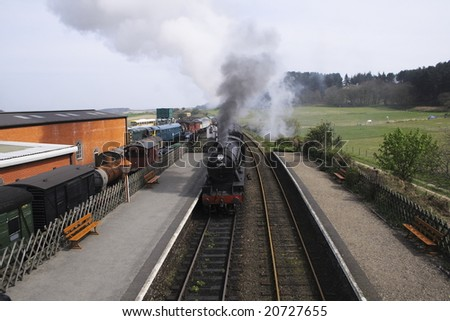 tourism locomotive entering a station where old locomotives are restored - stock photo