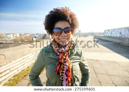 tourism, travel, people, international  and leisure concept - happy african american teenage girl or young woman in shades on city street - stock photo