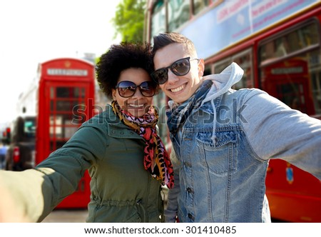 tourism, travel, people, leisure and technology concept - happy teenage international couple taking selfie over london city street background - stock photo