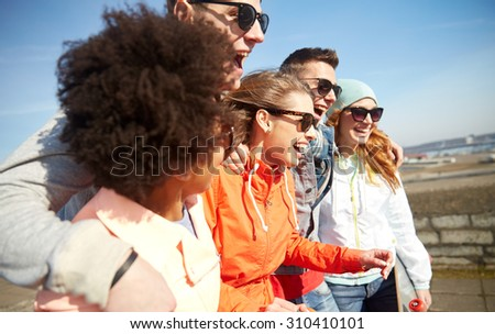tourism, travel, people, leisure and teenage concept - group of happy friends in sunglasses hugging and laughing on city street - stock photo