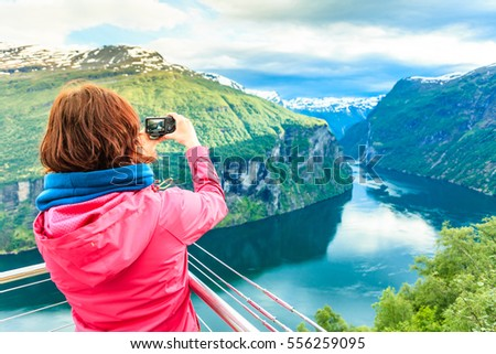 Tourism vacation and travel. Female tourist enjoying beautiful view over magical Geirangerfjorden from Flydalsjuvet viewpoint, taking photo with camera, Norway Scandinavia.