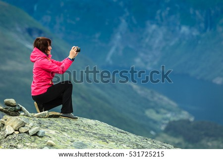 Tourism vacation and travel. Female tourist taking photo with camera, enjoying mountains landscape from Dalsnibba viewpoint, Norway Scandinavia.