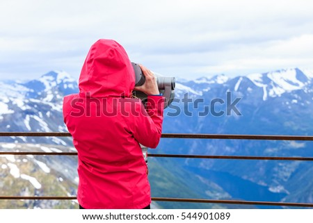 Tourism vacation and travel. Woman looking through sightseeing binoculars tourist telescope, overlooking Geirangerfjord and mountains landscape from Dalsnibba viewpoint, Norway