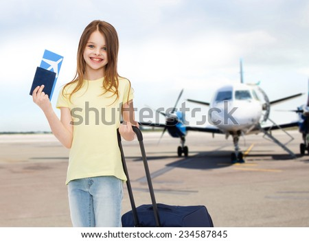 tourism, vacation, childhood and transportation concept - smiling little girl with travel bag, ticket and passport over airport background - stock photo