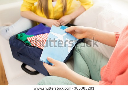 tourism, vacation, luggage and people concept - close up of women with airplane tickets and clothes in travel bag at home - stock photo