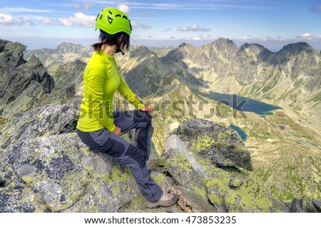 Tourist admiring the beautiful mountain valley. Young woman on a mountain top in High Tatra, Slovakia.