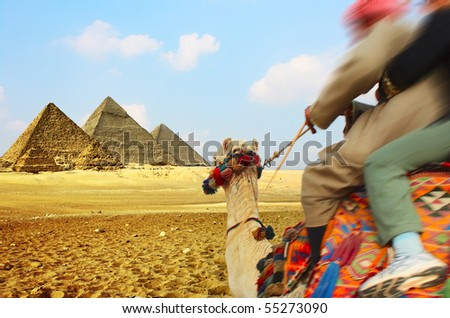 Tourist and bedouin riding on camel to pyramids - stock photo