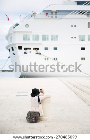 Tourist and passenger photographing a big cruise ship, docked in port for necessary maintenance, refill of supplies and sightseeing tour . Travel, hospitality and cruising business concept.  - stock photo