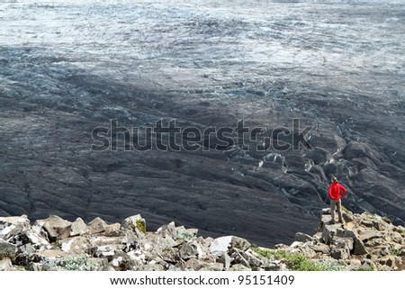 Tourist at Skaftafell is admiring a mighty glacier blackened from volcanic ash in Vatnajökull National Park, Iceland - stock photo