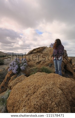 Tourist atop a granite outcrop at Augrabies National Park, Northern Cape, South Africa