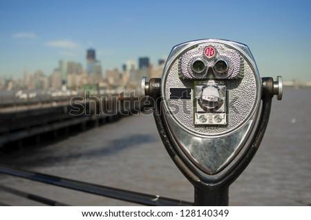 tourist binoculars at Liberty Island in front of Manhattan Skyline, New York City, USA - stock photo