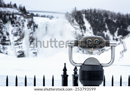 Tourist  binoculars  for viewing the frozen waterfall at the Monmerency Falls, Quebec City, Canada.  - stock photo