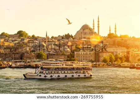 Tourist boat floats on the Golden Horn in Istanbul at sunset, Turkey - stock photo