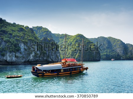 Tourist boat in the Ha Long Bay at the Gulf of Tonkin of the South China Sea, Vietnam. Beautiful landscape formed by karst isles. The Halong Bay is a popular tourist destination of Asia. - stock photo