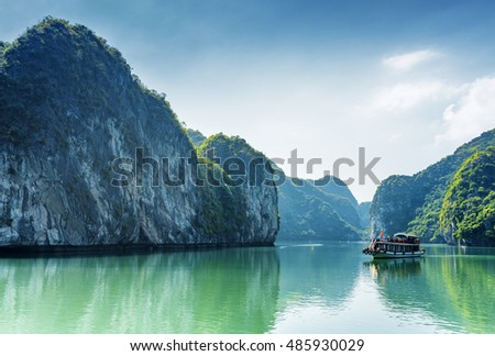 Tourist boat in the Halong Bay (Descending Dragon Bay) at the Gulf of Tonkin of the South China Sea, Vietnam. Landscape formed by karst isles. The Ha Long Bay is a popular tourist destination of Asia