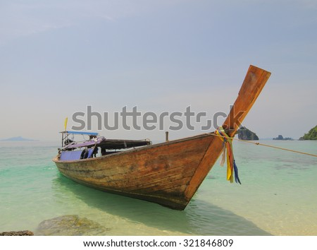 Tourist boat on the beautiful beach in sunny day in Krabi. Tourism is an important industry in Southern Thailand. - stock photo