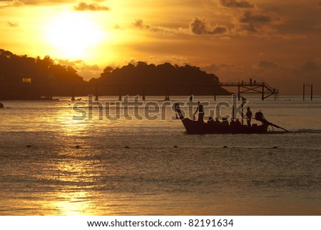 Tourist boat returning from a trip in the golden light of a Thai sunset at Pa tong beach - stock photo