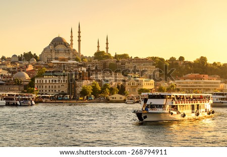 Tourist boat sails on the Golden Horn in Istanbul at sunset, Turkey - stock photo