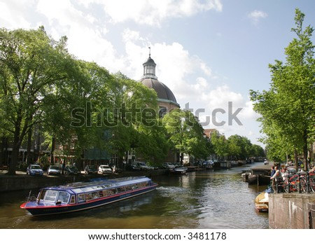 tourist boat takes people up the many canals in Amsterdam to see the views of the city by water.  Locals and travels look on. - stock photo
