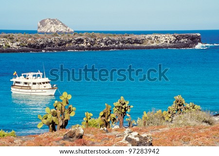 Tourist boat visits South Plaza with red sesuvium and prickly pear cactus vegetation in foreground, Galapagos Islands, Ecuador - stock photo