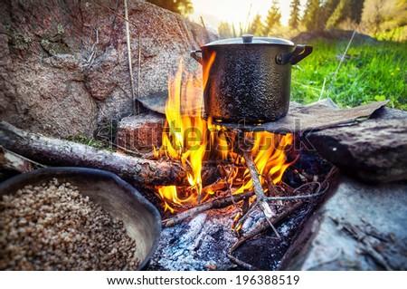 Tourist breakfast cooking on bonfire in the mountain forest, Almaty, Kazakhstan - stock photo