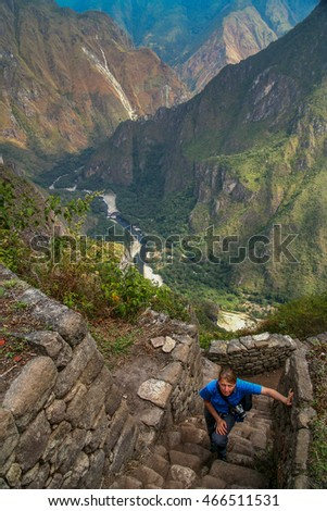 Tourist climbing old incan stairs to the top of Wayna Picchu for the views of Machu Picchu, Peru