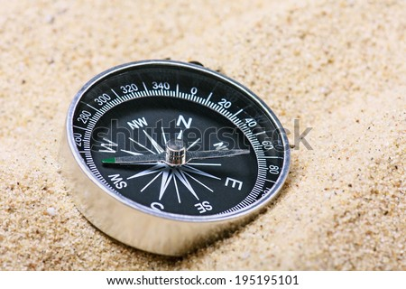 Tourist compass in the sand. Focus on the compass needle - stock photo