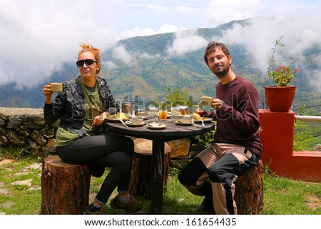 Tourist couple eating breakfast in himalayas mountains at Nagarkot, Kathmandu, Nepal - stock photo