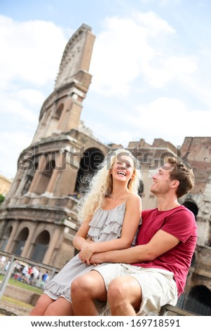 Tourist couple in Rome by Coliseum on travel dating laughing having fun. Happy young tourists traveling in Italy. Beautiful blonde woman and man in their 20s on holidays vacation in Italy, Europe. - stock photo