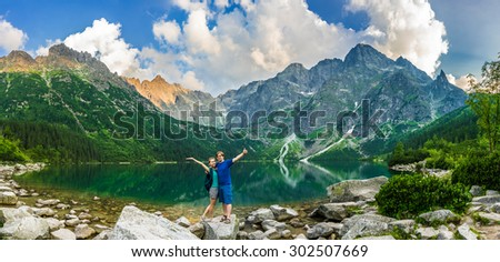 Tourist couple near the mountain lake Morskie Oko in Tatra National Park, Poland. Happy hiker man and woman rising hands on the picturesque lake in the mountains in summer. Travel Europe landscape. - stock photo