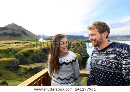 Tourist couple on romantic travel on Iceland. Happy couple sightseeing as tourists visiting landmarks and attractions in Arnarstapi, Snaefellsnes, Iceland. - stock photo