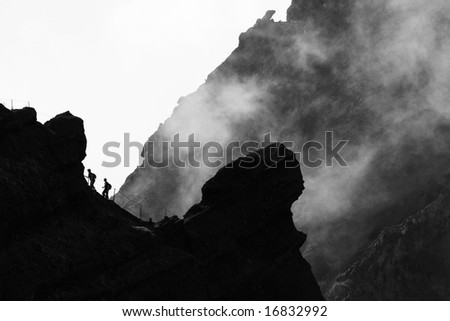 Tourist couple silhouettes climbing in the mountains