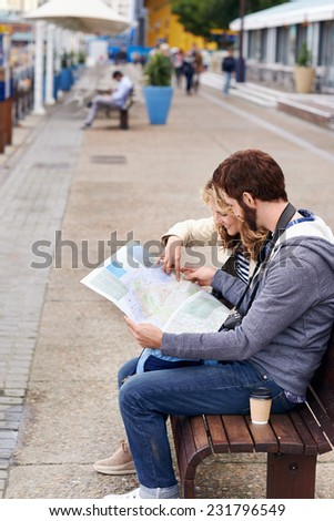 tourist couple sitting on bench looking at map - stock photo