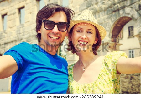 Tourist Couple Taking Selfie in Ancient Arena. Travel, Vacation and Technology Concept. - stock photo