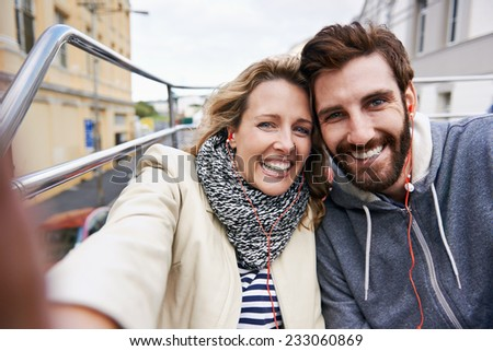 tourist couple travel selfie on open top tour bus in city - stock photo