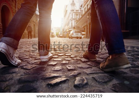 tourist couple walking on cobblestone street vacation in europe on holiday break - stock photo