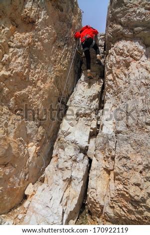 Tourist descends on the steel cable of via ferrata, Dolomite Alps, Italy - stock photo